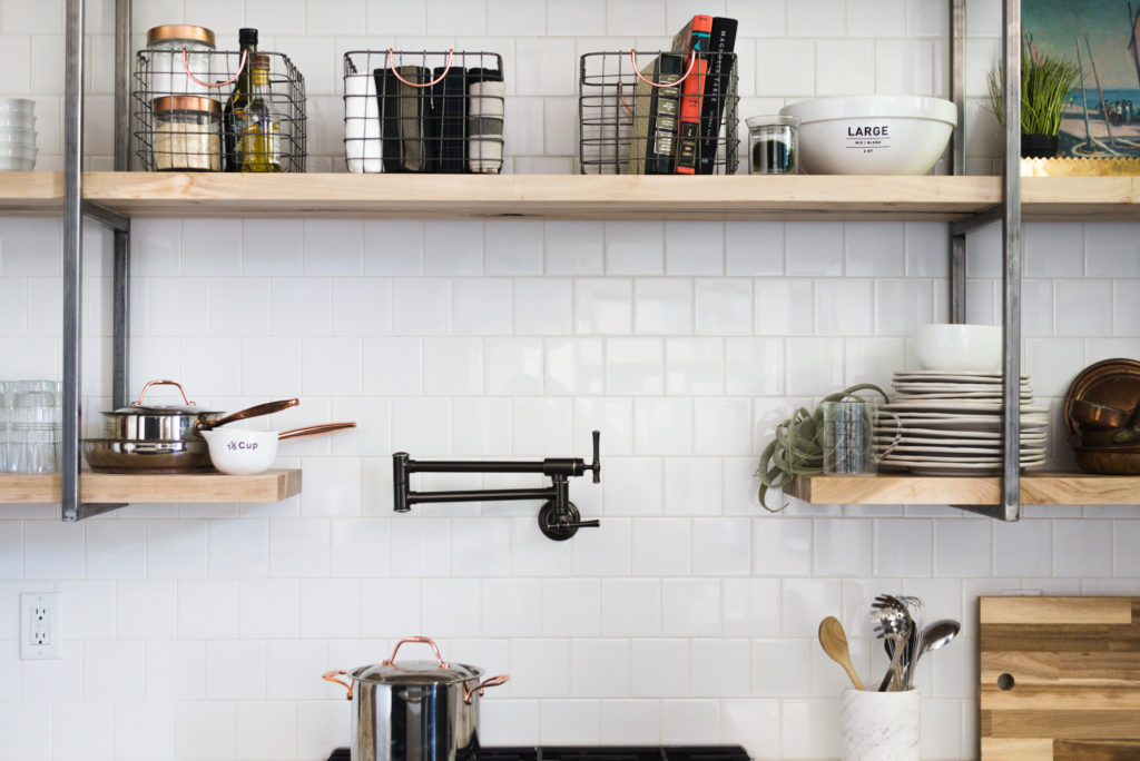 White square subway tile with white grout and open shelving with raw steel brackets make this renovation a vintage lovers dream! You've got to see the rest of the kitchen! (It has green cabinetry!)