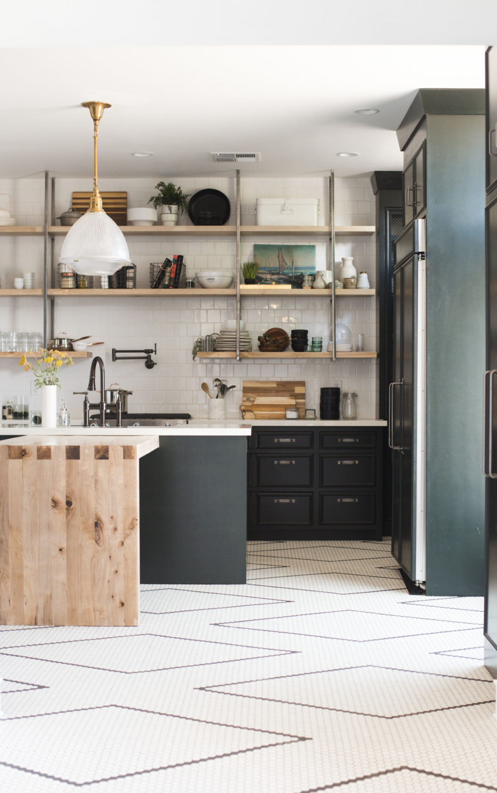 Dark green kitchen cabinets and hand laid black and white tile flooring (it's a DIY with a tutorial!!) are the star of this renovated kitchen. The bleached walnut island and open shelving fill the space with warmth. #kitchen #vintage #renovation #whitetile #openshelving