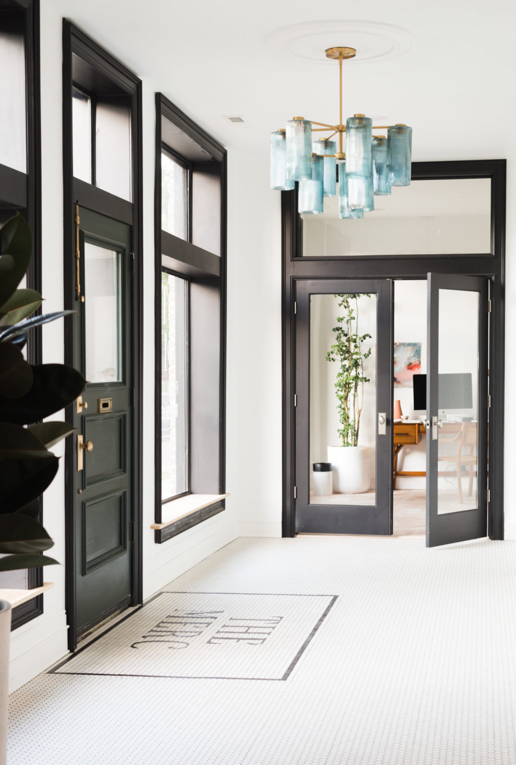 Black cased windows with window seat and dark green front door make this entryway pop. The custom lettered tile and blue glass chandelier add so much to this historic renovation! Get the full DIY details on Vintage Revivals!!s