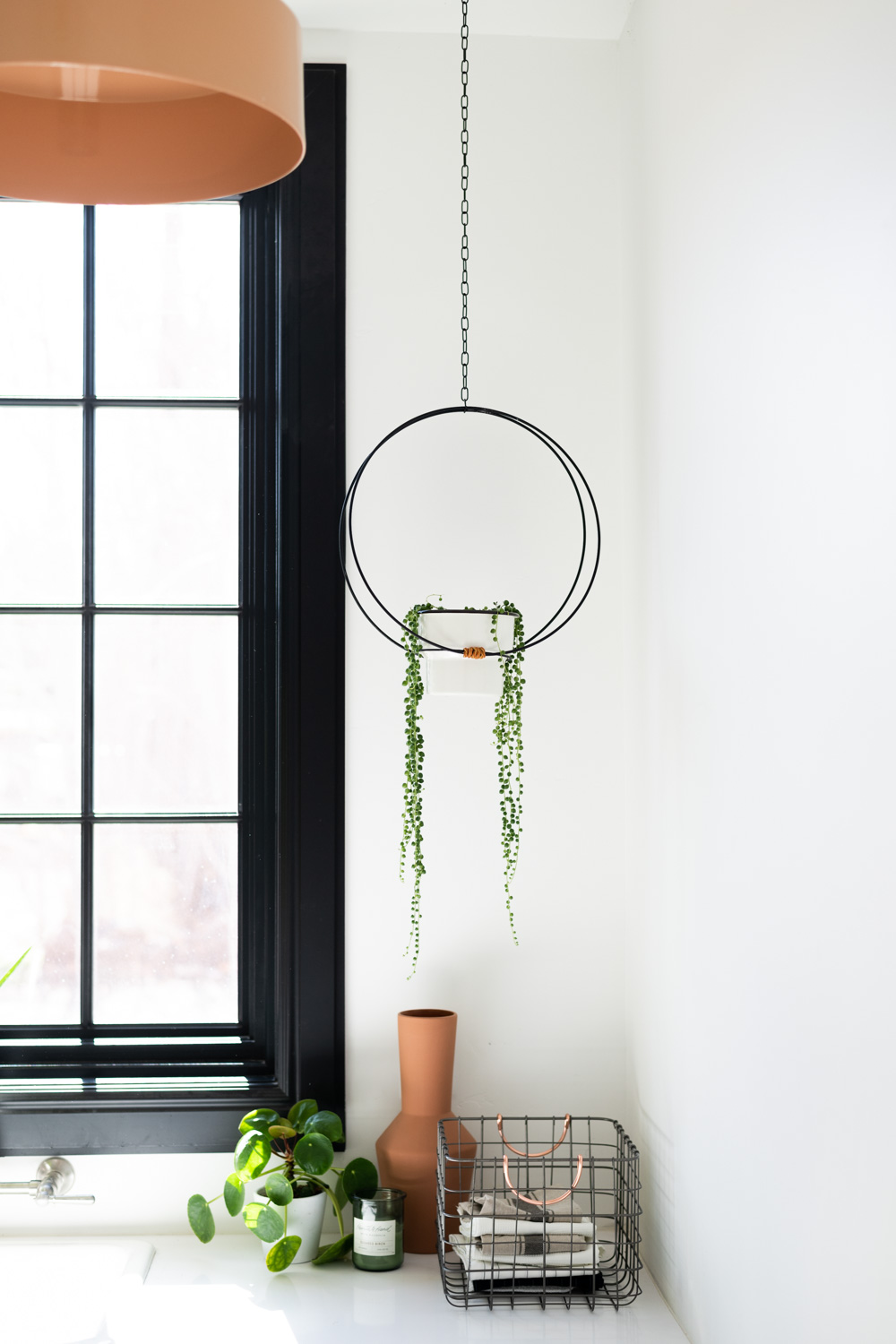 Black modern hanging planter with white pot and string of pearls succulent. Black window frame, wire basket with pilea and terra cotta vase